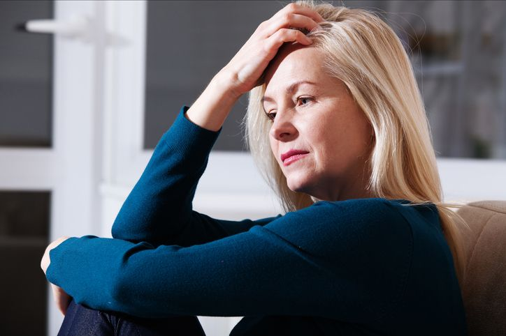 Sad depressed middle aged woman at home sitting on the..